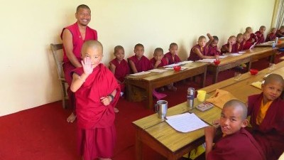 Image: Young monk waves to the camera
