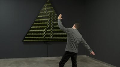 Image: Man in front of a work of modern art gesturing