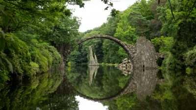 Image: Bridge over a river with the water looking like it has a hole in it