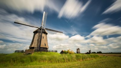 Image: Very old dutch windmill against a blue sky with streaking clouds