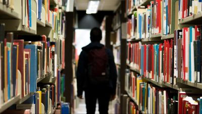 Image: Person walking through library shelves
