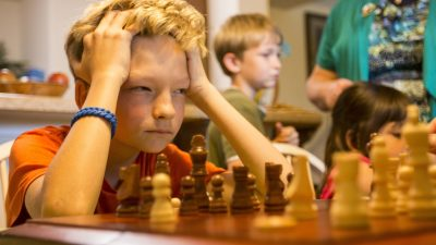 Image: boy concentrates intently on a game of chess with his head resting on his hands