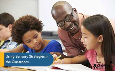 teacher helping student text using sensory strategies in the classroom