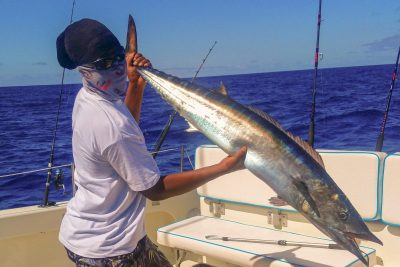 Crew member holding up a 22lb Wahoo
