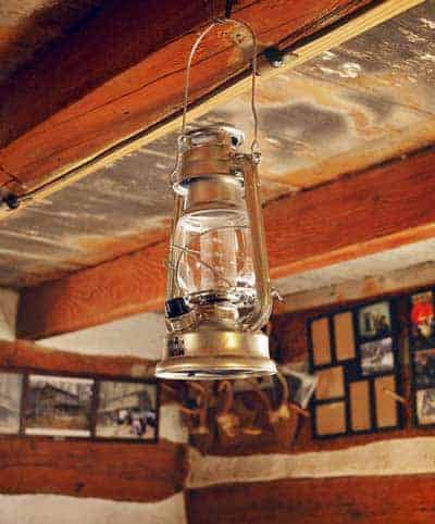 A lantern hanging from a ceiling of a wooden cabin