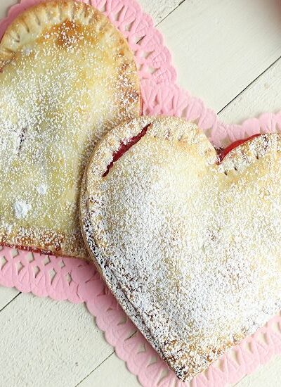 These Heart-Shaped Cherry Hand Pies are the perfect snack. Each hand pie is filled with sweet cherry pie filling sandwiched in between a flaky pie crust, then baked to perfection.