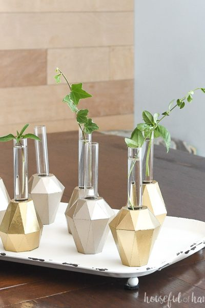 Gold propagation vases on a table with clipping in them.