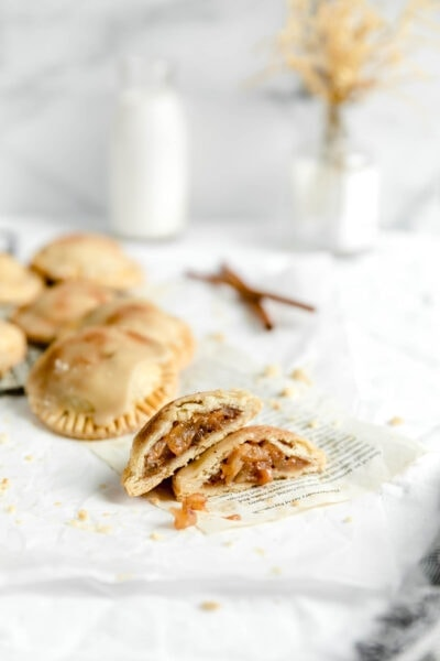 mini cinnamon apple pies cut open with cinnamon stick and a glass of milk