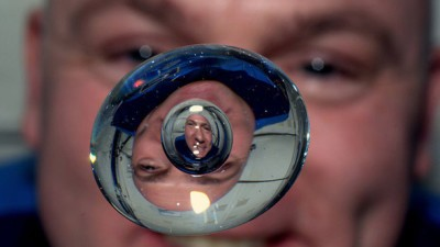 Image: Astronaut looks into bead of water hovering in space