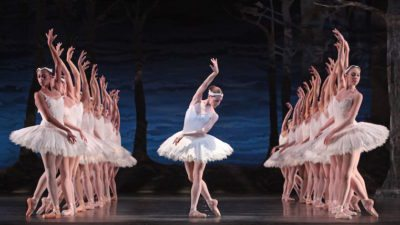 Image: Huston Ballet production of Swan Lake, principal dancer centered with corps de ballet surrounding