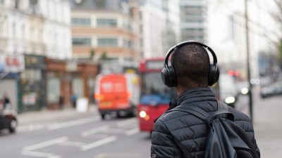 Image: man wearing headphones on a busy city street