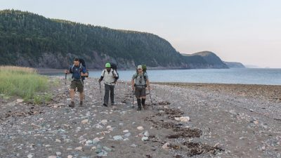 Image: Three men walk across a stone covered beach in on the Fundy Footpath with the Bay of Fundy behind them