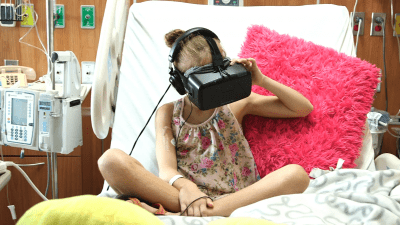 Image: young girl in a hospital bed wearing a VR headset