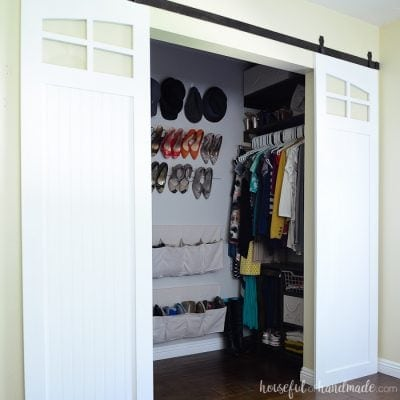 Small master closet with white barn doors open showing the DIY closet organization system.