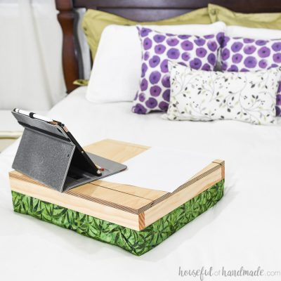 DIY lap desk with storage on a bed with an iPad and paper on it.