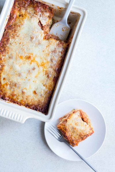 zucchini lasagna recipe in a casserole dish, next to a slice of lasagna on a plate.