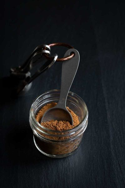 Pumpkin Pie Spice Mix in a mason jar with measuring spoons