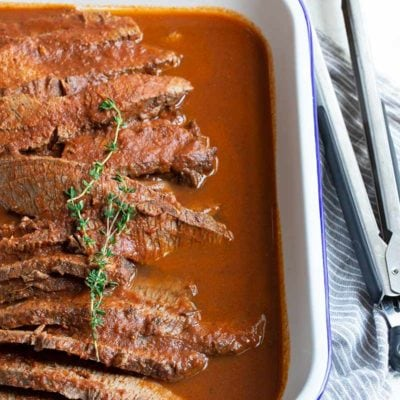 Braised beef brisket recipe in a rectangular serving dish, with kitchen tongs on the right