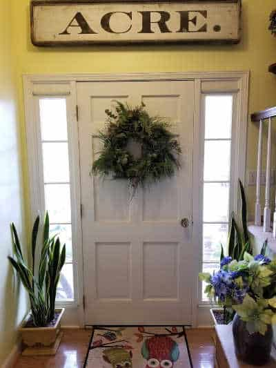 entryway with wood sign above door reading ACRE, with home made evergreen wreath hanging on a white door, with snake plants flanking the door in front of side lights