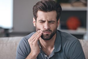 Man With Tooth Pain - Emergency Dentist in Greensboro for Tooth Pain and Other Dental Emergencies