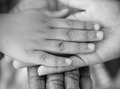 Black and white adult and child hands