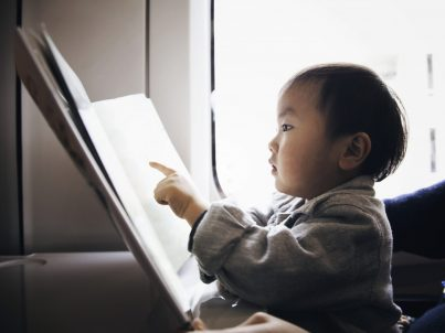 Asian boy reading a picture book.