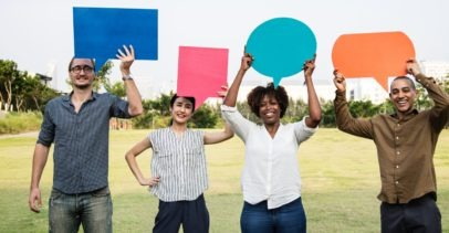 Four People Smiling and Holding Different Speech Bubbles