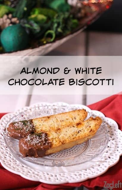 Two Almond and White Chocolate Biscottis with the tip dipped in milk chocolate on a small plate on a red cloth napkin