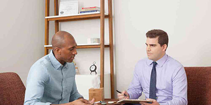 Male rehab patient in a meeting with drug addiction counselor at Mountainside