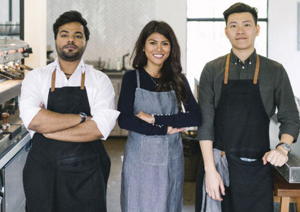 team of three people in aprons left two crossing arms