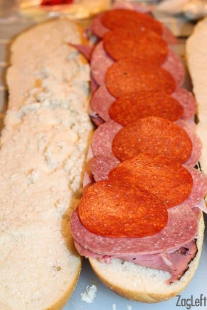 Layering meats on a loaf of french bread