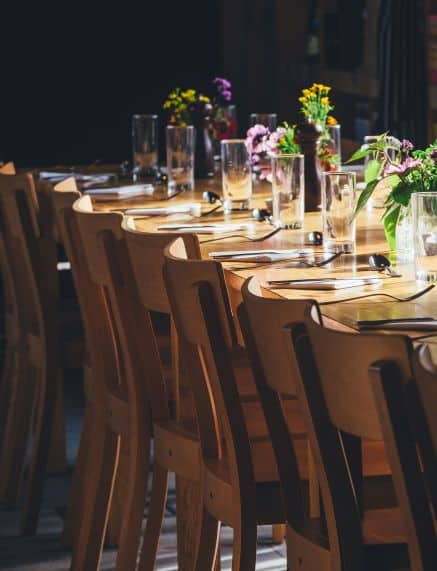 Large dining room table set, decorated with glass vases and alternating types of flowers