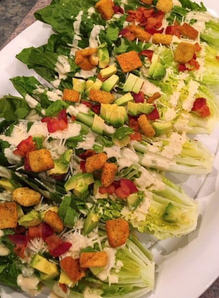 Romaine Lettuce heads cut in half and topped off with avocados, croutons, and cheese