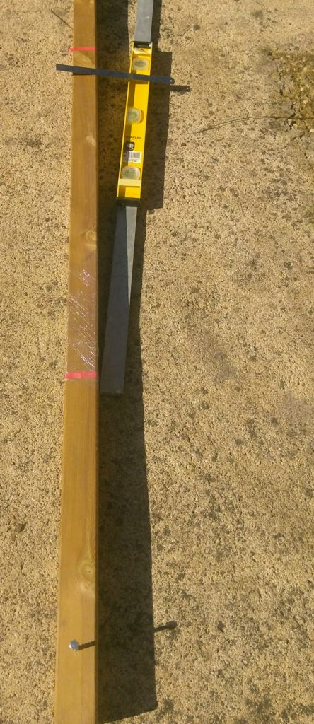 Sun shade post ready for concrete with hold-down bolts, protective plastic and tape for measuring angle of lean