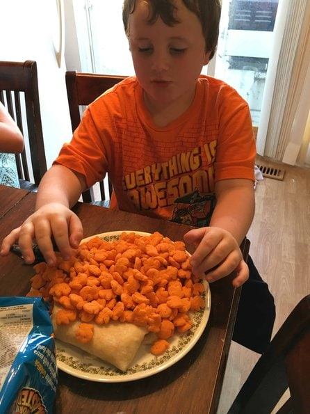 little boy poured to much goldfish crackers on his plate