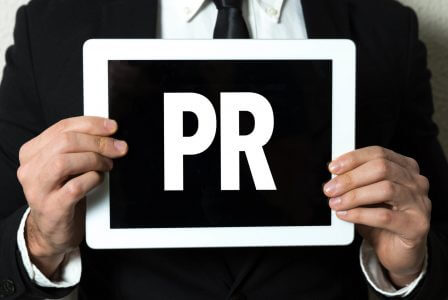 Man Holding PR Sign