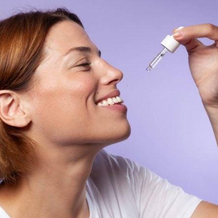 Portrait femme souriant prenant de l'huile de CBD 10% Equilibre