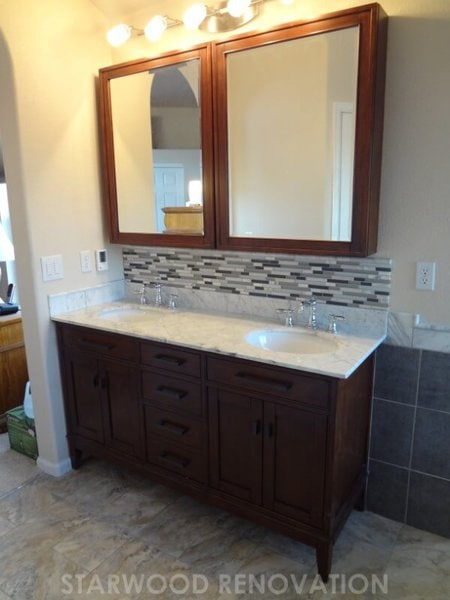 Vanity and glass tile backsplash for remodeled bathroom in Denver with free standing tub. Undermount sinks in a granite countertop add a luxurious touch.