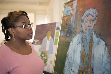 "Dimond Leslie, a senior studio art major, looks at the paintings ""Man at a Table"" by Robert LaHotan, left, and ""Self Portrait"" by John Heliker, right, on display on April 13, 2016. (AJ Reynolds/Brenau/University)"