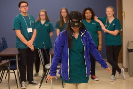 Leslie Espinoza attempts to navigate a course while wearing goggles simulation alcohol intoxication during the psychology specialization during the final day of the first Brenau Medical Scholars Program at Brenau University East Campus on Wednesday, April 13, 2016, in Gainesville, Ga. (AJ Reynolds/Brenau University)