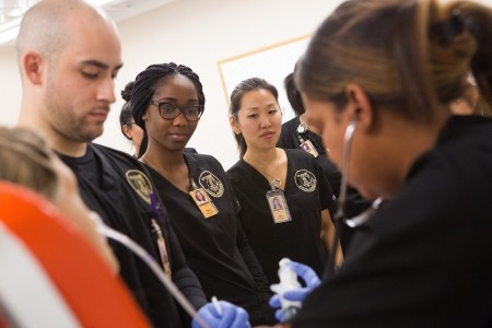 From left, nursing students Richard Gonzalez, Dara Atijosan and Jane Lim look on while Shemila Thompson practices nasogastric tube placement during a skills lab at Brenau East. (AJ Reynolds/Brenau University)