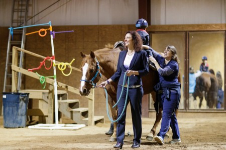 Nicole Walker, BU '01, occupational therapist and owner of Walker Therapy in Gainesville, Georgia, leads a horse while fellow therapist Nolina Varley, BU '01, helps make sure a client maintains his balance during an equine therapy session. (Photos by AJ Reynolds/Brenau University)