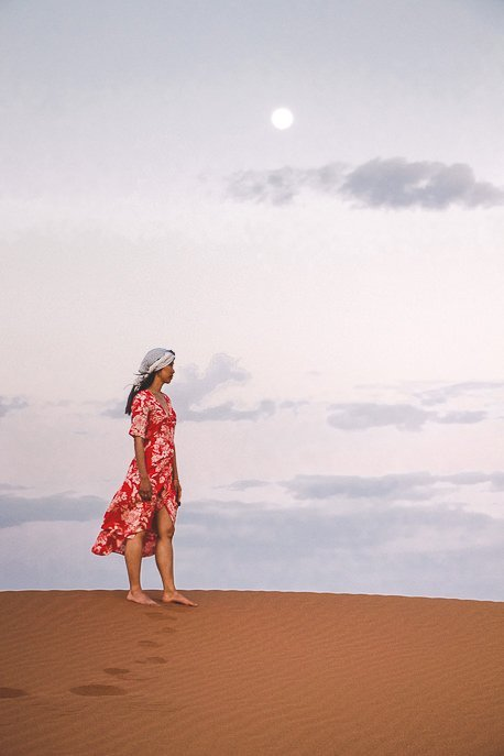 A woman in a red dress underneath the moon at dusk in the Sahara Desert, Morocco