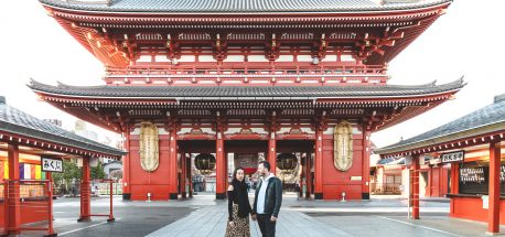 A couple stand in front of Sensoji Temple in Asakusa Tokyo Japan