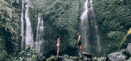 Best Free Travel Apps | A couple stand under Fiji Waterfalls in Bali, Indonesia