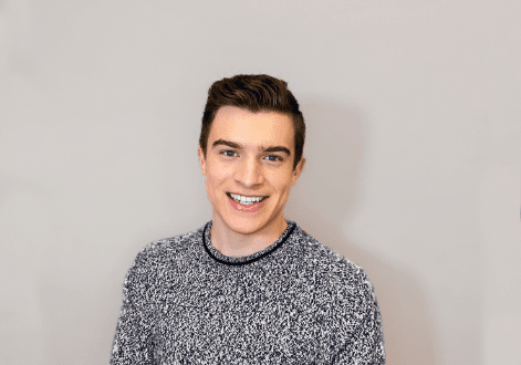 Headshot of Connor Ripple smiling in front of a grey background.