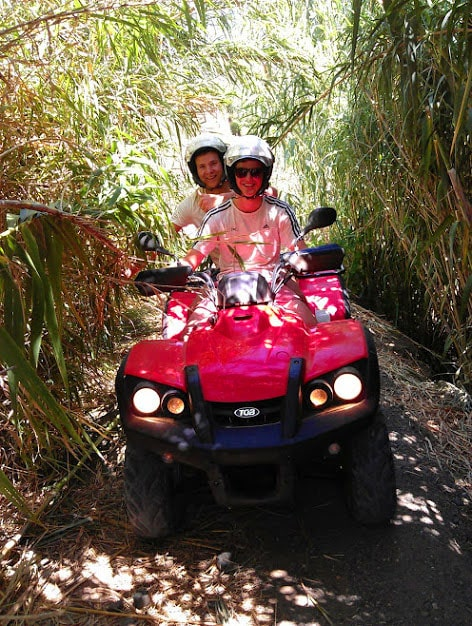 a red quad with a couple amongst high greenery