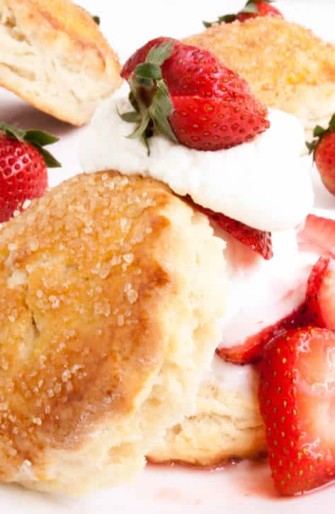 A close up image of Strawberry Shortcake topped with whipped cream and strawberries from themerchantbaker.com
