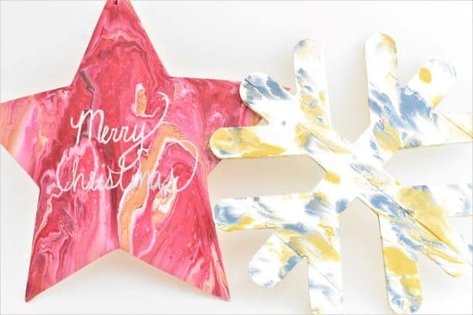 Two wooden Christmas Decorations decorated with acrylic pouring, one star and one snowflake