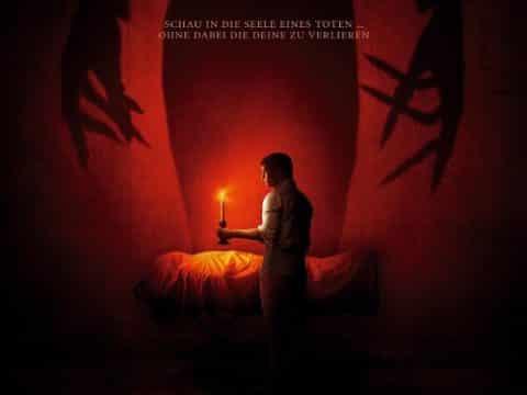 """Filmposter zu """"The Vigil - die Totenwache"""": ann mit Kerze vor dämonischem Schatten"""